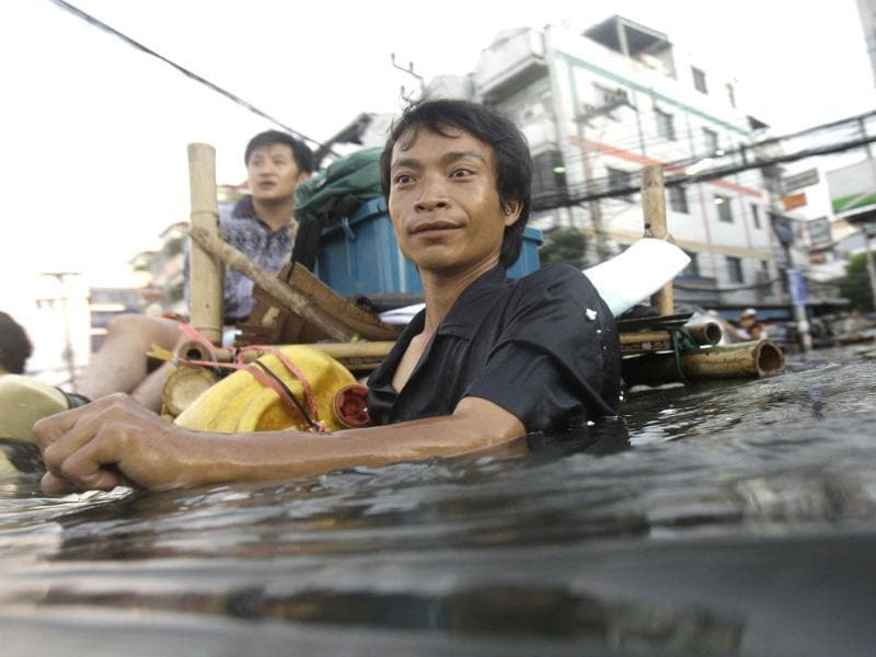 A Thai man wades along chest-deep floodwaters on the outskirts of Bangkok, Thailand. (AP)