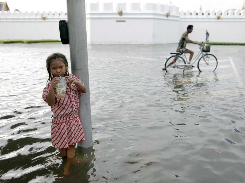 A girl has a drink as she stands near a cyclist in a flooded street outside the Grand Palace in Bangkok.