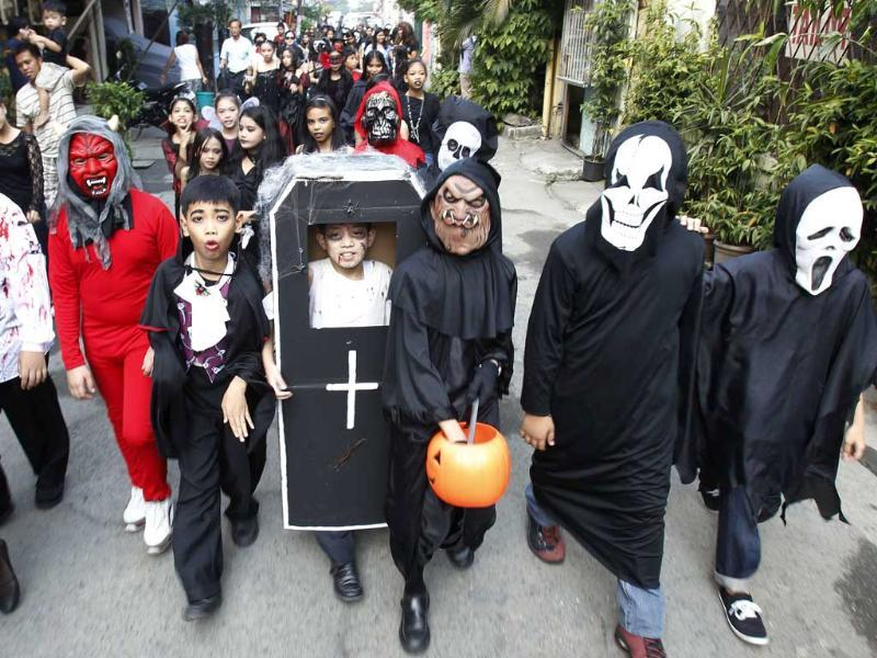 Students from the Brainshire Science School dress in Halloween costumes as they parade along the main street of Paranaque, in Metro Manila.