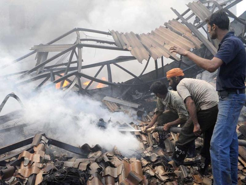 Rescue workers extinguish a fire which engulfed the Kochar Sung-Up Acrylic factory outside Amritsar. The fire was allegedly caused by a an electrical short circuit, officials said.