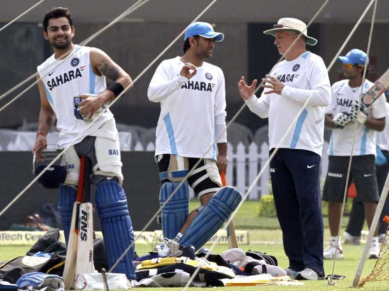 Mahendra Singh Dhoni listens to team coach Duncan Fletcher, as teammate Virat Kohli smiles, during a practice session ahead of their Twenty20 international cricket match against England in Kolkata.