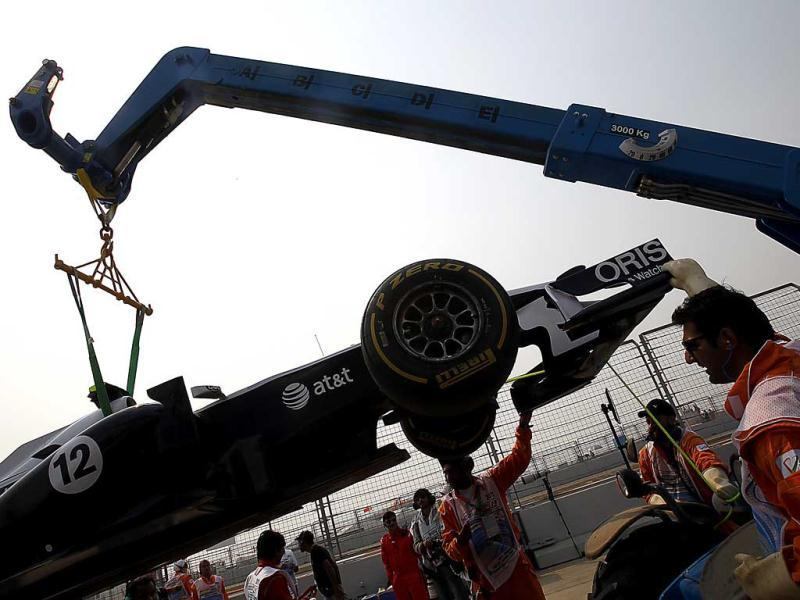 The car of Williams driver Pastor Maldonado of Venezuela is removed from the track after he suffered engine problem his car during a practice session ahead of Sunday's Indian Formula One Grand Prix at the Buddh International Circuit in Noida, 38 kilometers (24 miles) from New Delhi