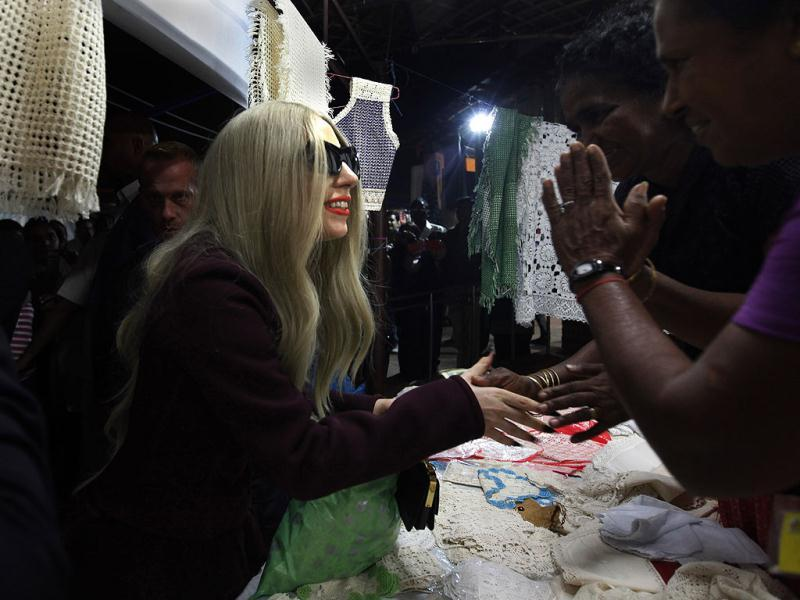 Lady Gaga (L) greets shopkeepers at the Dilli Haat handicrafts market in New Delhi. (AP)