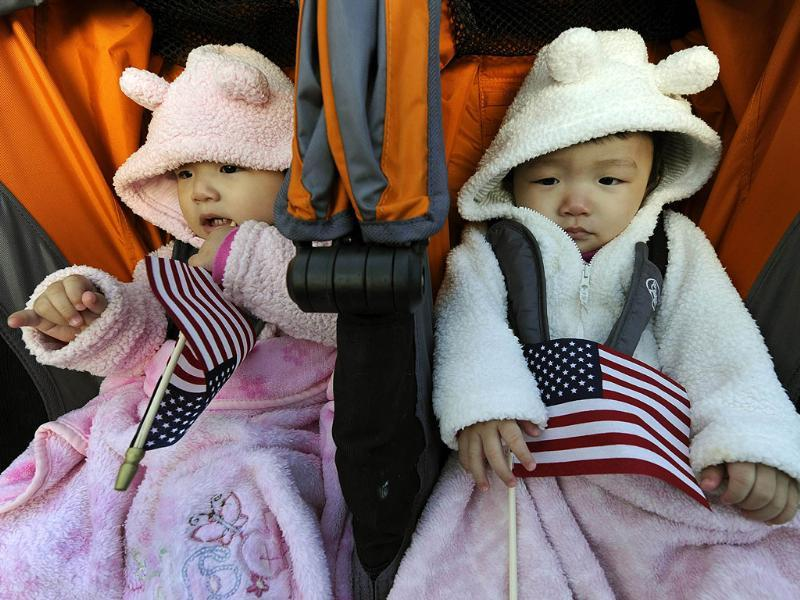 Rachel and Julia Young sleep as their mother Young Sun Kim from South Korea is sworn in during a naturalisation ceremony conducted to swear in 125 new citizenship candidates at a ceremony on Liberty Island in New York to commemorate the 125th anniversary of the dedication of the Statue of Liberty. (AFP Photo/Timothy A Clary)