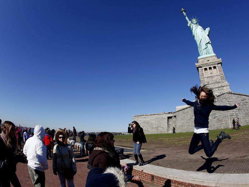 A visitor leaps for a photograph beneath the Statue of Liberty during ceremonies marking the 125th anniversary of the Statue at Liberty Island in New York. (Reuters/Mike Segar)