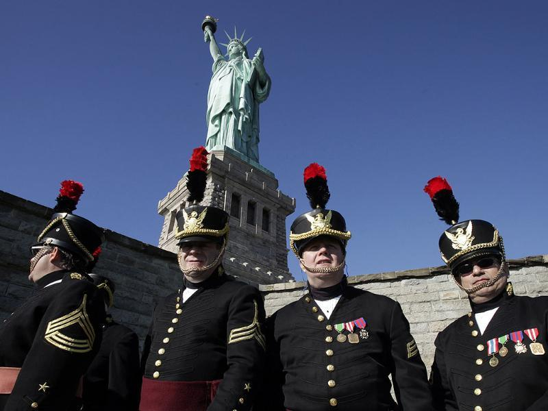 Members of the Veteran Corps of Artillery of New York attend a ceremony at the Statue of Liberty to mark her 125th anniversary in New York. (AP Photo/Mark Lennihan)