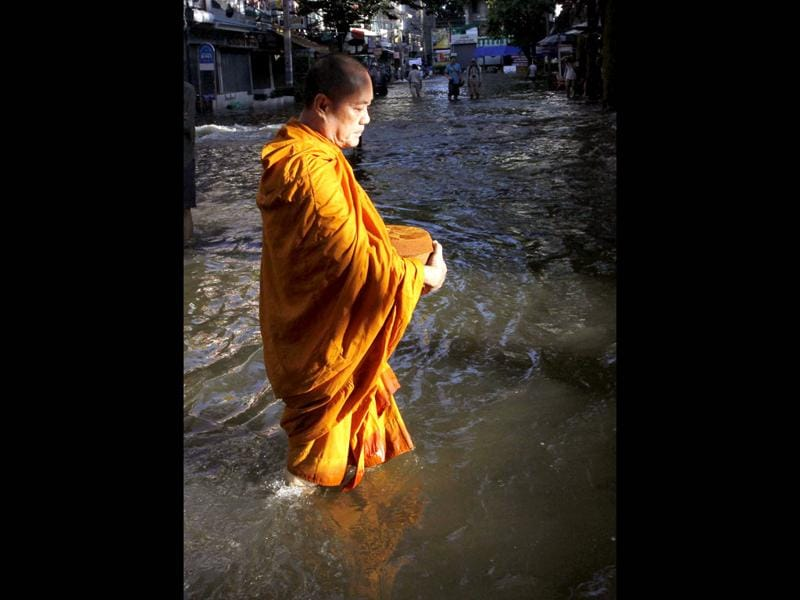 A Buddhist monk walks in a flooded street to collect morning alms in Bangkok. Bangkok's Chao Phraya River is expected to burst its banks over the weekend during the unusually high tide that begins on Friday, causing some flooding in nearby areas. Thailand's worst floods in half a century, caused in part by unusually heavy monsoon rain, have killed 377 people since mid-July and disrupted the lives of nearly 2.2 million, until now mostly in the north and central provinces.
