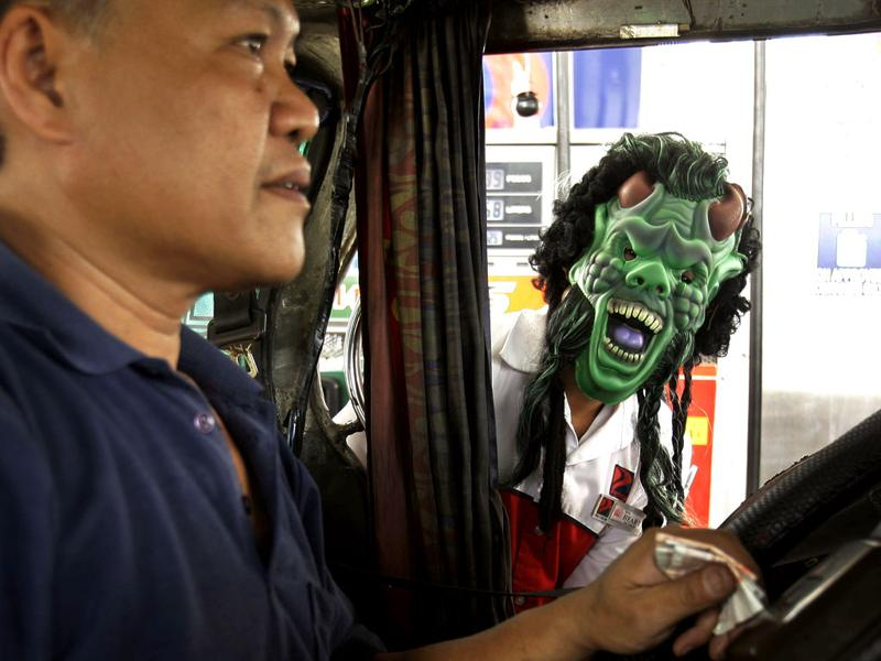 A gas station attendant wears a mask as part of their holiday treat as he talks to the driver of a commuter jeep Saturday, in suburban Mandaluyong City, east of Manila, Philippines. Attendants in the gas station wore masks to attract customers as Filipino Catholics prepare to observe All Saints' Day.