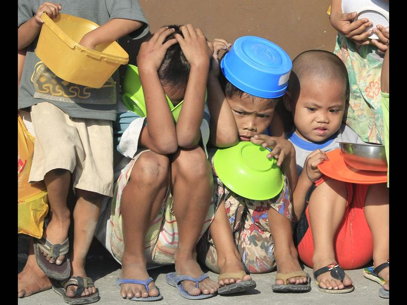 Children hold their food containers as they wait for the distribution of free chocolate porridge at a local government feeding program in Tondo, Manila. The world's population will reach seven billion, according to projections by the United Nations, which says this global milestone presents both an opportunity and a challenge for the planet.