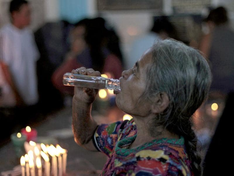 A woman drinks aguardiente, an alcoholic drink, while praying in the church of San Simon in Iztapa, in the region of Escuintla, 62 km (39 miles) from Guatemala City. People in Guatemala revere San Simon, also known by its Mayan name Maximon o Ry Laj Man, on October 28 annually. For some devotees, San Simon is synonymous with prosperity and happiness, while others associate him with witchcraft, paganism and a protector for drunkards. Since the 19th century, devotees have offered money, liquor or tobacco in exchange for his blessings.
