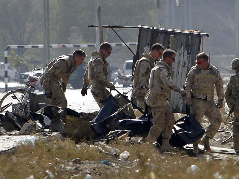 Foreign troops carry a casualty from the site of a suicide attack in Kabul.