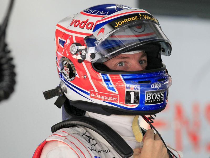 McLaren driver Jenson Button of Britain adjusts his helmet at his team garage during a practice session ahead of Sunday's Indian Formula One Grand Prix at the Buddh International Circuit in Noida.