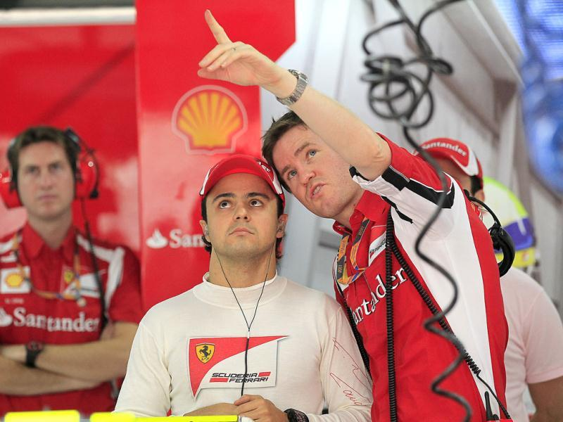 Ferrari driver Felipe Massa of Brazil speaks with a team crew at his team garage during a practice session ahead of Sunday's Indian Formula One Grand Prix at the Buddh International Circuit in Noida.