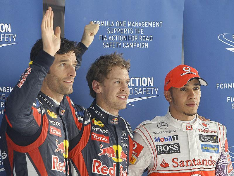 Red Bull driver Sebastian Vettel of Germany (C) pole position, Red Bull driver Mark Webber of Australia (L) third fastest time, and McLaren Mercedes driver Lewis Hamilton of Britain, second fastest time, pose for the media after the end of the qualifying round at the Buddh International Circuit in Greater Noida. (AP)