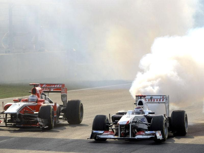 Sauber-Ferrari driver Kamui Kobayashi of Japan (R) runs with smoke at the second turn right after the start of Formula One's Indian Grand Prix at the Buddh International circuit in Greater Noida.