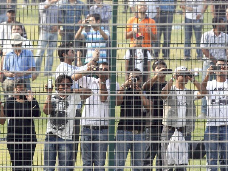 Spectators look from a fence during the Indian Formula One Grand Prix at the Buddh International Circuit in Noida.
