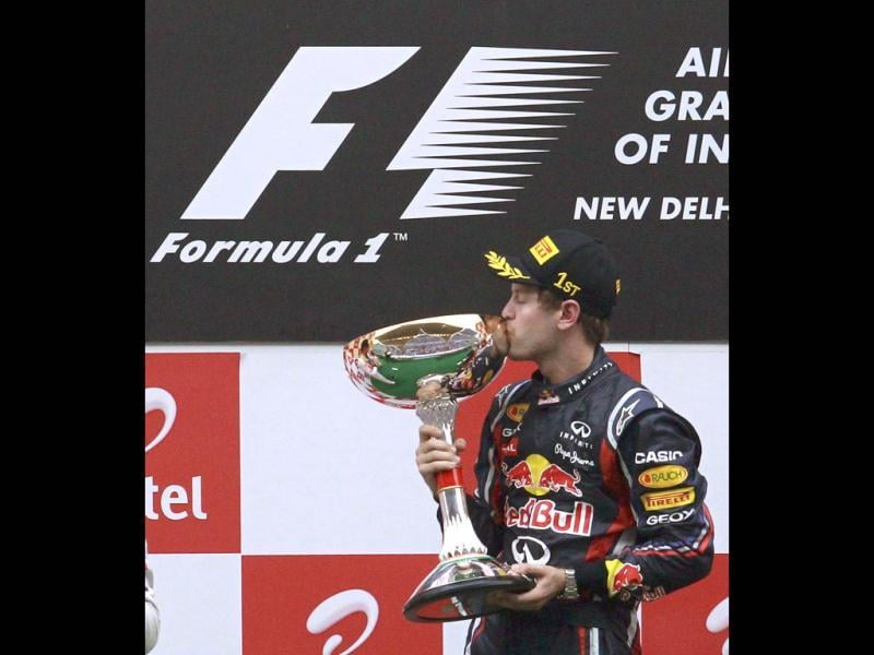 Red Bull Formula One driver Sebastian Vettel of Germany kisses his trophy after winning the Indian first Formula One Grand Prix at the Buddh International Circuit in Greater Noida.