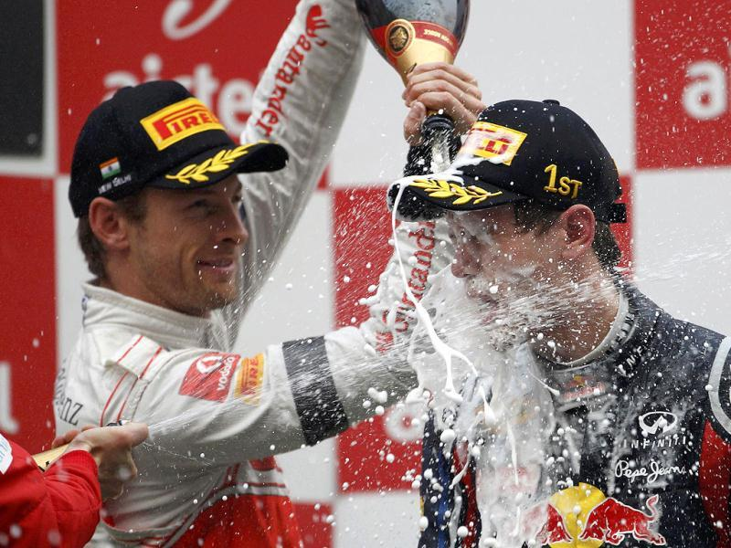 Second placed McLaren Formula One driver Jenson Button of Britain (L) pours champagne over Red Bull Formula One driver Sebastian Vettel of Germany, winner of the Indian first Formula One Grand Prix at the Buddh International Circuit in Greater Noida.