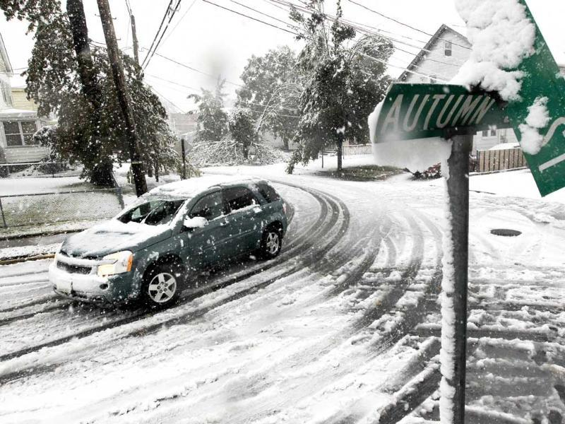 A vehicle makes its way at the snow-covered intersection of Autumn and Grove Streets in Lodi, New Jersey, following a rare October snowstorm that hit the region.