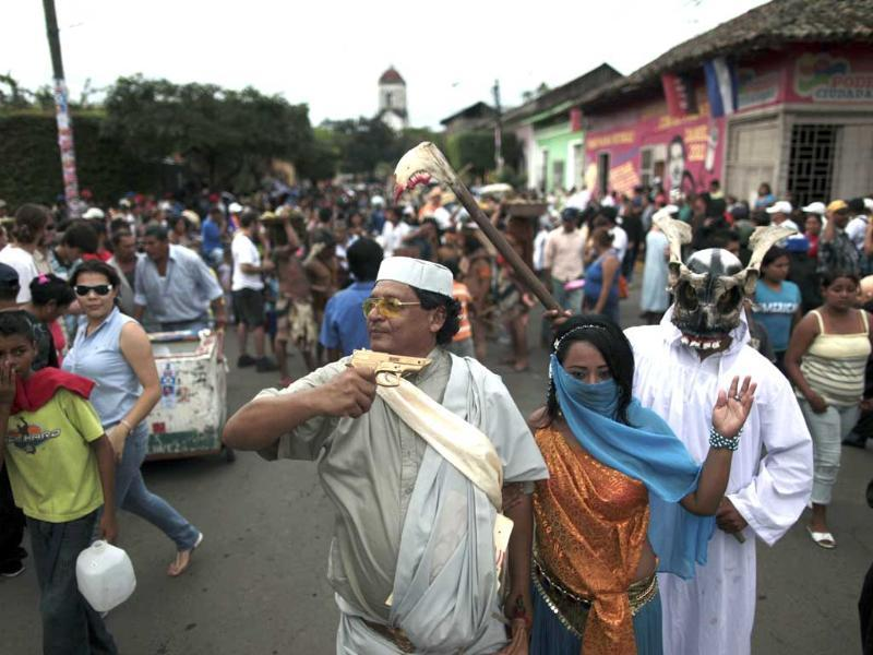 A man dressed as the late Libyan leader Muammar Gaddafi holds up a toy gun alongside a woman dressed as Gaddafi's wife Safiya as they are followed by a person dressed as the Grim Reaper during a religious celebration called Torovenado, in honour of Masaya's patron saint, San Jeronimo, in Nicaragua.