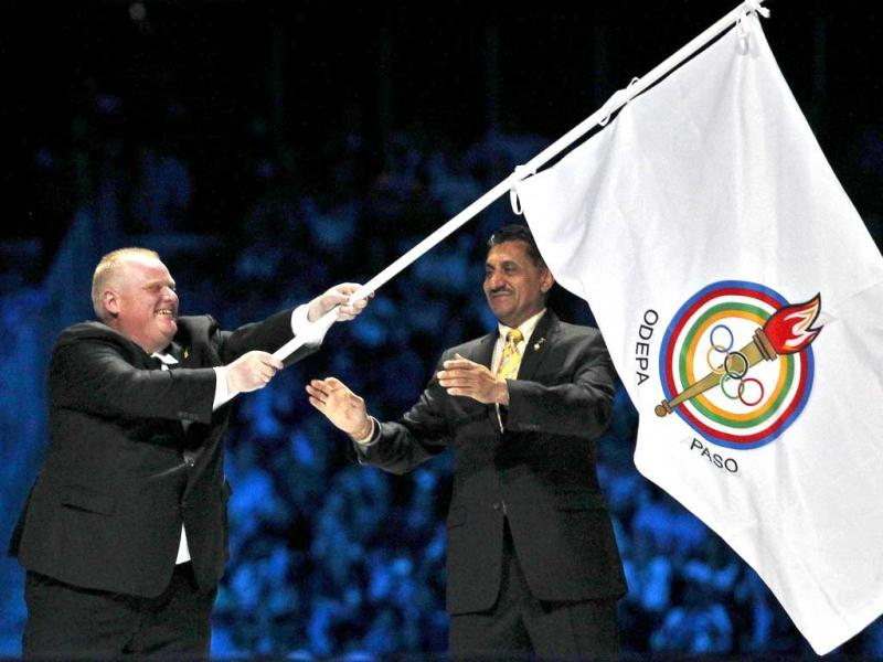 Toronto Mayor Rob Ford (L) waves the Pan American Games flag next to Canada's Minister of Sport Bal Gosal during the closing ceremony of the Pan American Games in Guadalajara.
