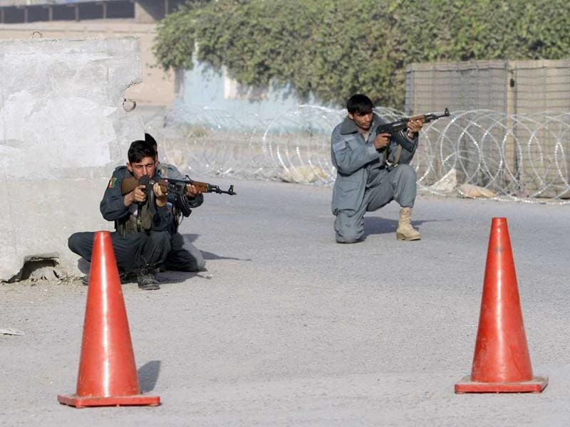 Afghan security men take position during an exchange of fire with armed insurgents next to the site of a suicide bomb attack, in Kandahar, Afghanistan.