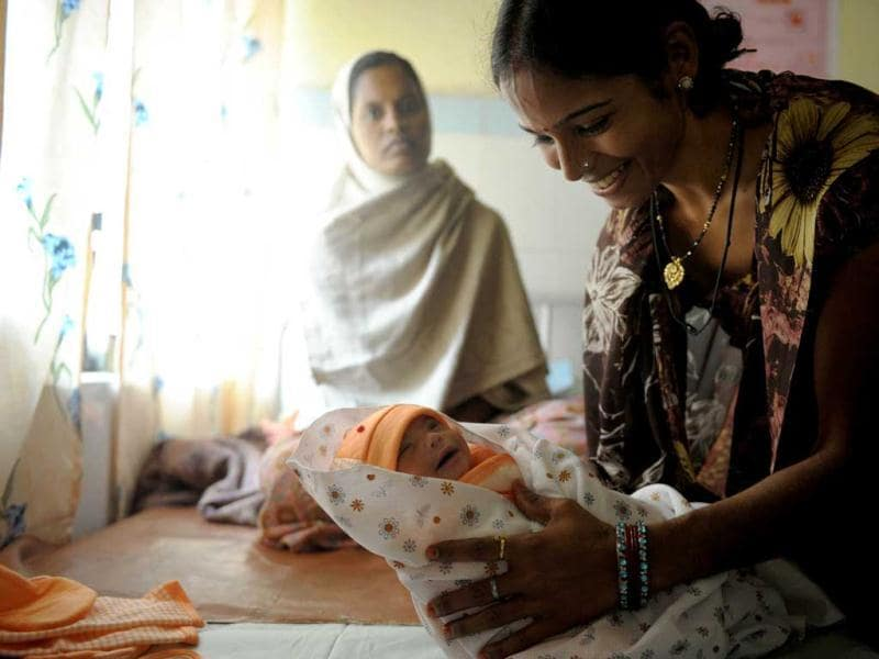 A volunteer at a Community Health Center in Mall, near the central east Indian city of Lucknow holds a new born baby girl as her mother watches. According to Plan International, a non govermental organisation for children's welfare the seventh billion inhabitant of earth was born in India.