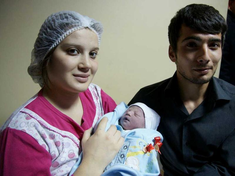 Gamze Ozkan, 18, holds her new born baby boy, Yusuf Efe, with her husband, Mustafa Ozkan, 23, at the Zekai Tahir Burak maternity hospital in Ankara, Turkey. According to the UN Population Fund, Yufuf Efe, son of the unemployed mother and a worker husband, will be one of 7 billion people sharing Earth's land and resources.