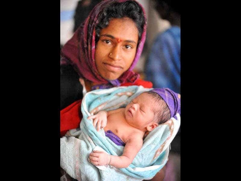 S.Uma holds her new born baby boy at Governement Gandhi Hospital in Hyderabad. The United Nations says that by its best estimates the seven billionth baby will be born somewhere on October 31, and countries around the world have planned events surrounding the demographic milestone.