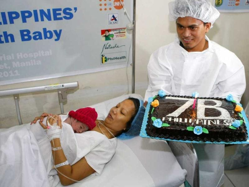 Danica Camacho is cuddled by her mother Camille as her father Florante Galura holds a cake shortly after she was born at the Government's Fabella Hospital in Manila. The Philippines, ranked 12th as the most populated country in the world, joins the rest of the world as it welcomes its symbolic 7 billionth baby in simple ceremony in Manila.