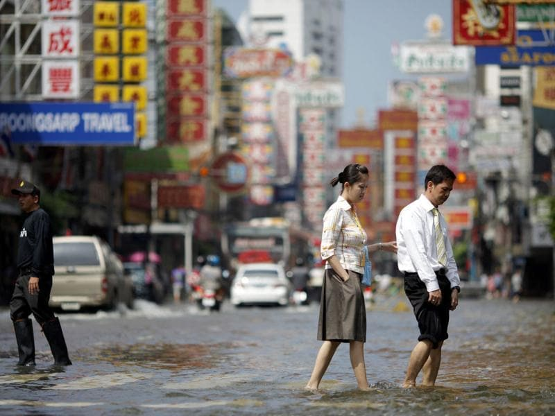 People cross the flooded main street in Chinatown in central Bangkok.