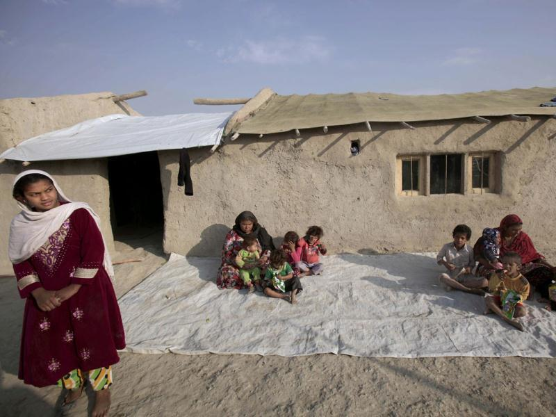 Afghan women sit with their children in front of their homes in a poor neighborhood in Kabul.
