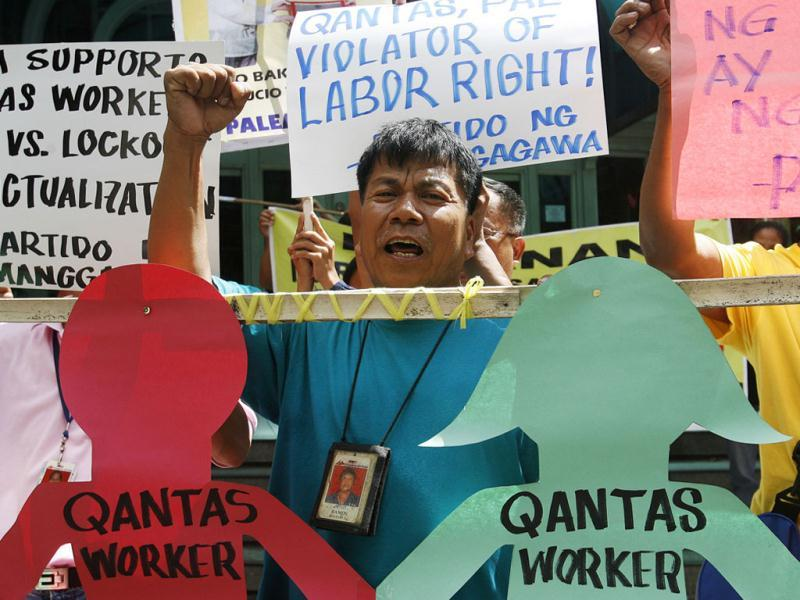 A dismissed worker of the Philippine Airlines rally in support of Qantas workers outside the Qantas office in Manila's Makati financial district.