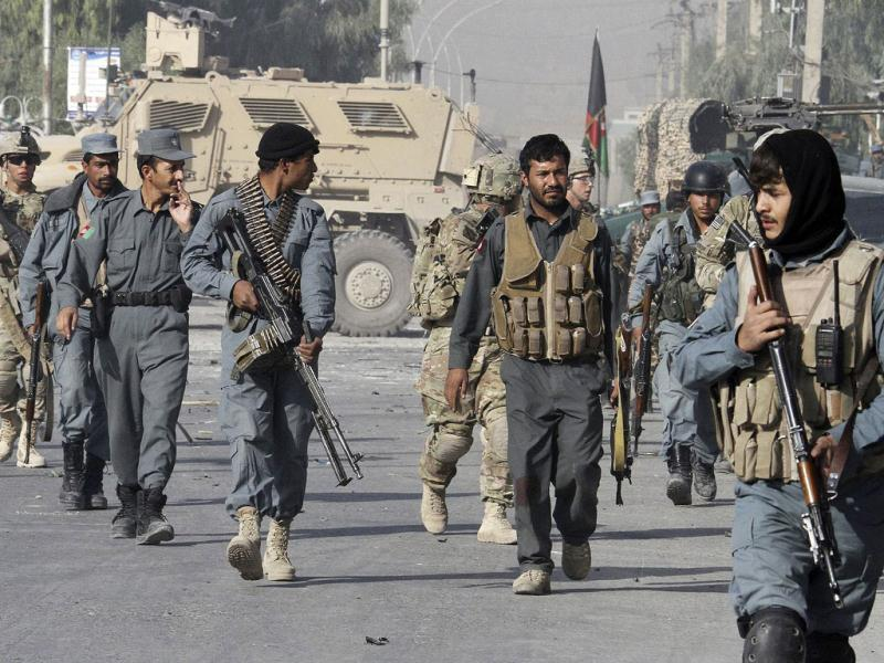 Afghan policemen and US soldiers arrive at the site of a suicide bomb attack near a building used by the Office of the United Nations High commissioner for Refugees (UNHCR) in Kandahar.