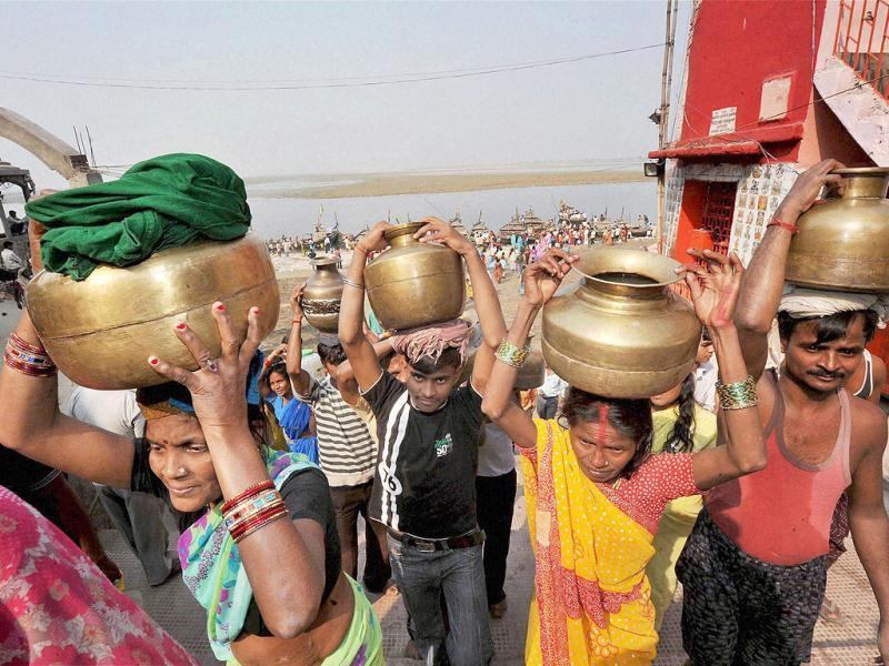 Devotees carrying holy Ganga water for preparing 'prasad' for the Sun god on the occasion of 'Kharna' puja of Chhath festival in Patna.