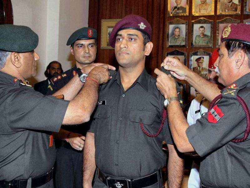 Army chief Gen VK Singh (L) pinning badges on MS Dhoni in New Delhi today after he was granted honorary rank of Lt Colonel in the Territorial Army.