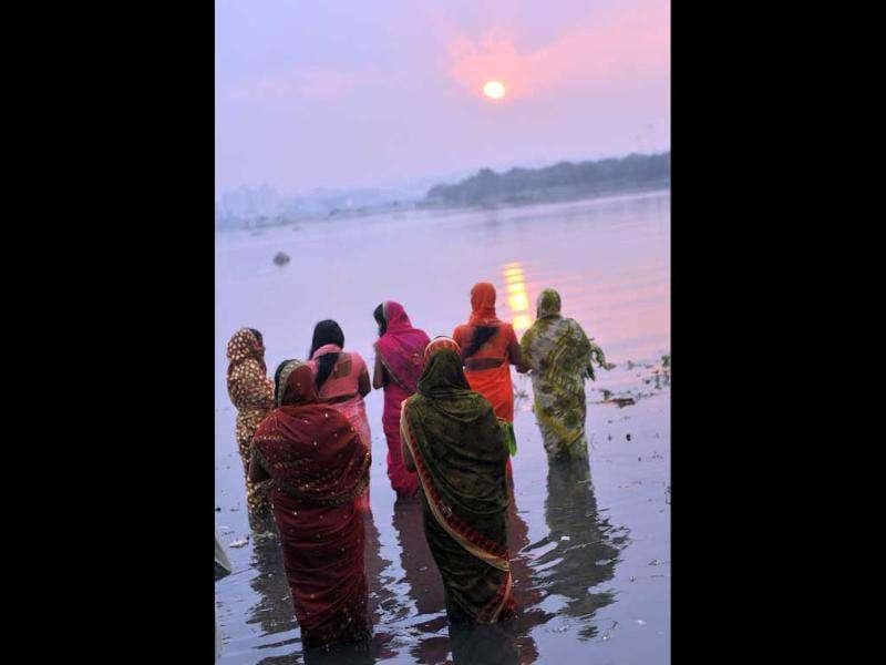 Hindu devotees offer prayers to the sun during the Chhath festival on the banks of the Hussain Sagar lake in Hyderabad . The Chhath festival is observed in India, where homage is paid to the sun and water Gods eights days after Diwali, the festival of lights.