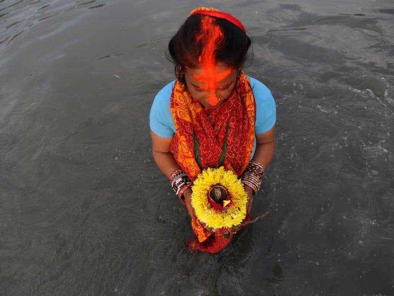 A Nepalese Hindu woman worships the sun as she stands in the Bagmati River during the Chhath festival, which honours the Sun God, in Kathmandu. People pay their respects to both the rising and setting sun during the Chhath festival when people express their thanks and seek blessings from the forces of nature.