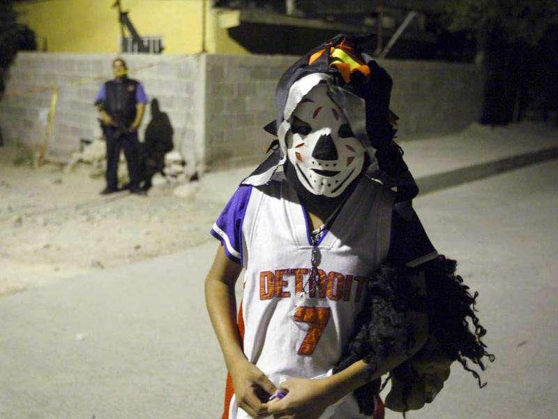 A child dressed in a Halloween costume stands at a crime scene in a neighbourhood in Ciudad Juarez. A municipal police officer and his mother were shot dead at her house by a group of hitmen, according to local media.