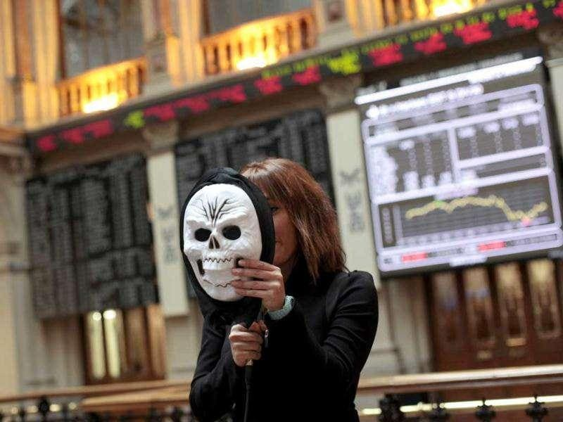 A TV reporter uses a Halloween mask to explain the bourse situation as she goes live from Madrid's stock exchange. European shares suffered their biggest one-day loss in a month after Greece's prime minister unexpectedly called a referendum on the latest bailout deal, raising anxiety over the euro zone debt crisis.