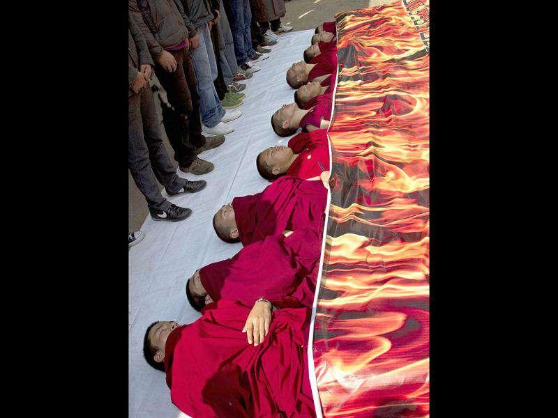 Buddhist monks lie under a banner showing flames during a political enactment depicting immolations in Tibet in Dharmsala.