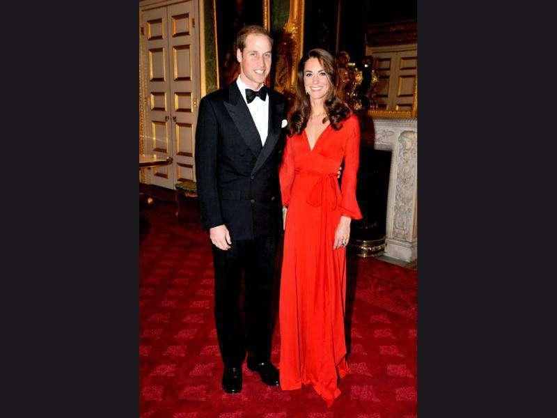 Kate Middleton in a scarlet evening gown with husband Prince William.