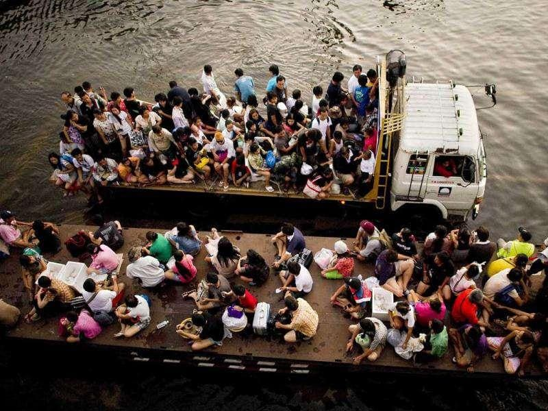 People sit on the back of trucks as they cross floodwater in a street next to the Chao Praya river in Bangkok.