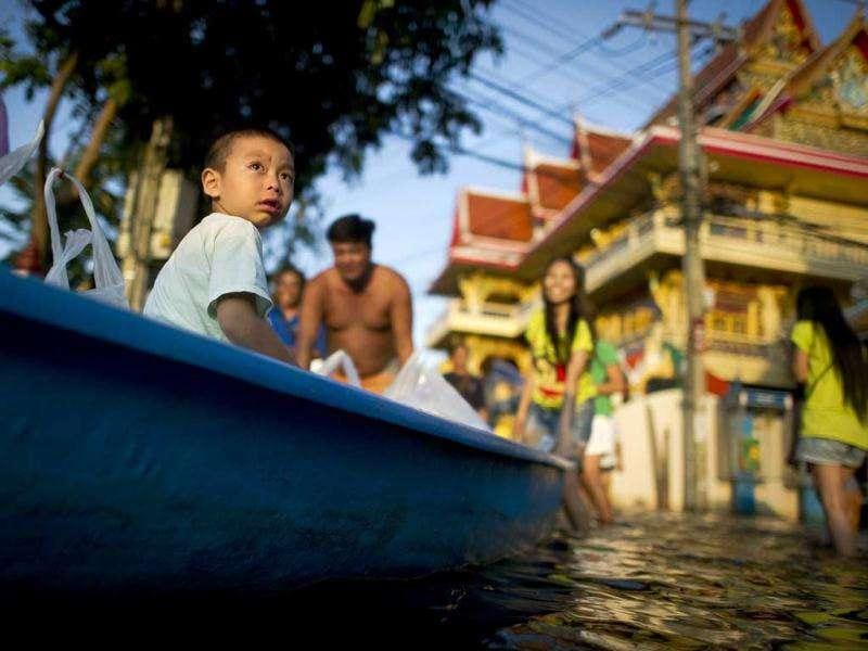 A boy sits inside a boat on floodwater next to the Chao Praya river in Bangkok.