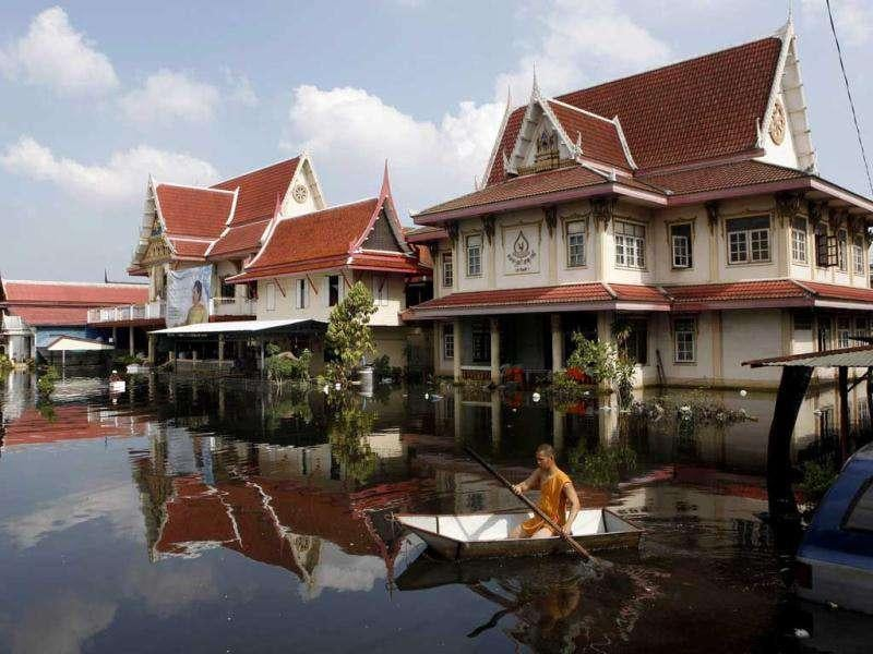 A Buddhist monk paddles a boat past a flooded temple in Bangkok.