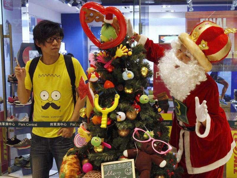 A man watches a participant poses as Santa Claus in front of a Christmas tree as part of the competition during the Hong Kong round of the Santa Claus Winter Games at a shopping mall in Hong Kong. Hong Kong won the championship in 2009 and came in third in 2010 for the international competition held annually in Gaellivare, Sweden.