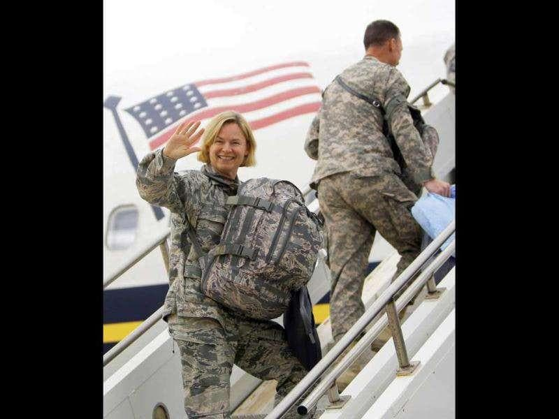 A US army soldier waves as she begins her journey home at al-Asad Air Base west of Baghdad, Iraq.