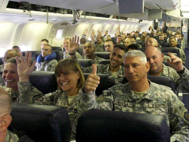 US army soldiers gesture as they begin their journey home at al-Asad Air Base west of Baghdad, Iraq.