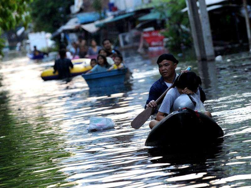 Local residents commute through floodwaters in Bangkok. The death toll from Thailand's worst floods in decades surged above 400.