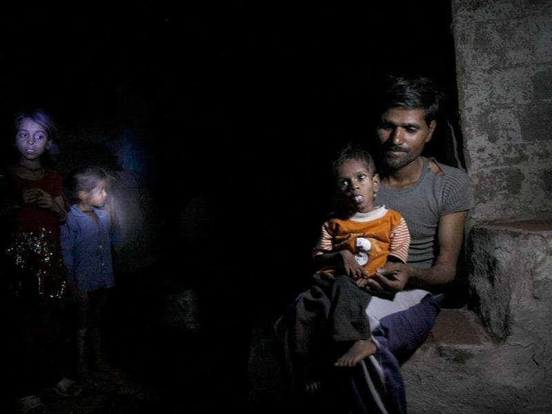 Three-year-old Abhishek, who is malnourished, with his father Sanjay Jatav outside their hut in Kasba Thana village in Rajasthan's Baran district. Much of the Rs 72 crore, meant to stop chronic malnutrition and hunger deaths among Rajasthan's 90,000 Sahariya tribals, has not been spent. HT photo: Himanshu Vyas